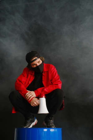 An emotional young man 25-30 years old in a black protective mask, a cap and a red jacket sits on a blue barrel and holds a megaphone against a dark background. Protest concept