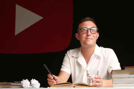 A 30-35-year-old millennial man with a short haircut, wearing glasses, a light shirt, sits at a table and comes up with a script for his vlog. vlogging live feeds on social media network Фото со стока