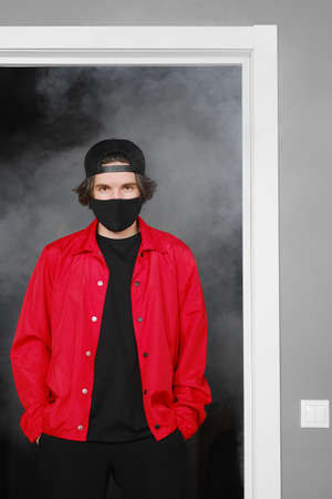Portrait of a young man of 25-30 years old in a black protective mask, cap and red jacket. A man posing on a gray background in the smoke. Coronavirus protection. Фото со стока