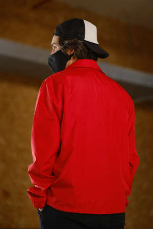 Portrait of a young man 25-30 years old in a black protective mask, black cap and red jacket. Young fashion man posing with his back against a bright background. Clothing for mockup. Fashion photography concept