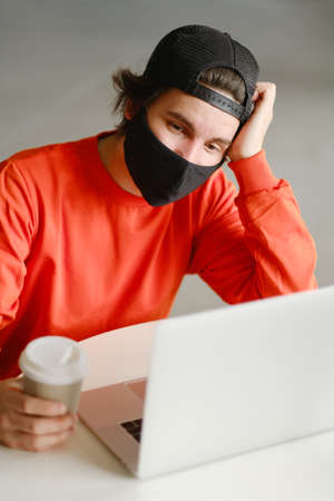 Portrait of a 25-30 year old man wearing a black protective mask, cap and red sweatshirt. The man sits alone at a table in the open space, drinking coffee and working on his laptop. Freelance concept Фото со стока