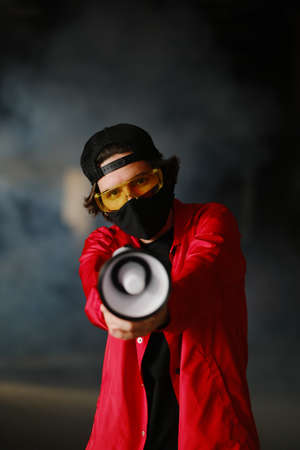 A young man of 25-30 years old in a black protective mask, yellow goggles, a cap and a red jacket holds a megaphone against a dark background. Protest concept