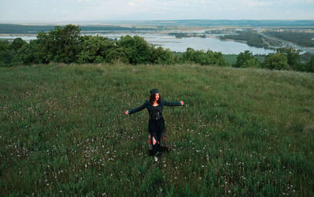 A young woman of 25-30 years old with curly red hair, in a green dress and in a diadem with feathers is standing against the background of beautiful nature at dawn. Solitude with nature.  Фото со стока