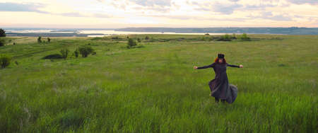 A young woman of 25-30 years old with curly red hair, in a green dress and a diadem with feathers, is spinning and dancing against the background of beautiful nature at dawn. solitude with nature Фото со стока