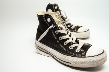 lacing sneakers: old black canvas shoes Stock Photo