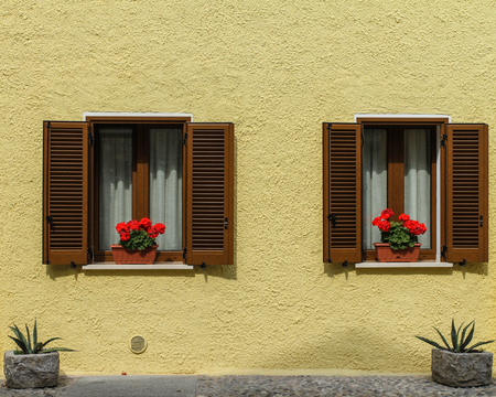 two windows with red flowers and yellow wall Stock Photo