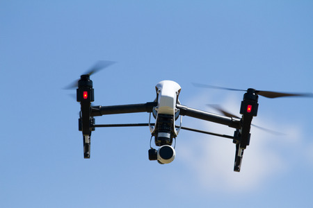 Quadrocopter UAV with 4K camera flying high in the sky