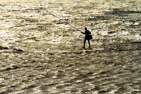 fisherman with a rod stand alone in the sea