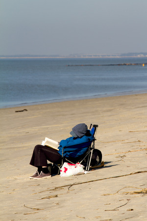 senior person resting on the beach during sunny winter day