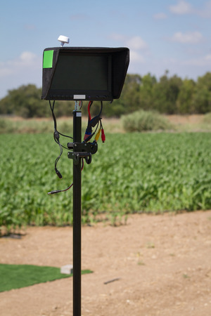 Outdoor monitor with light shield installed on a stand in use for drone control and video streaming