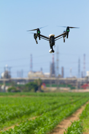 Drone for agriculture is hovering over plantation on the background of a chemical facility