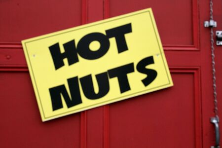 A sign proclaiming hot nuts for sale. Imagens