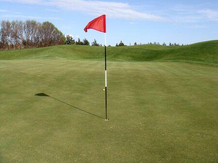 ゴルフ場のグリーン上に赤いフラグ
