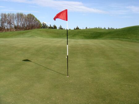 The red flag on the green of a golf course Imagens