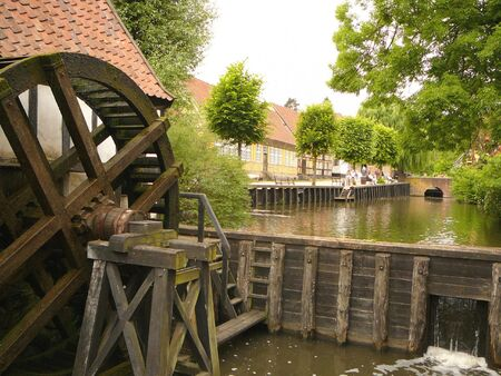 A water wheel sits in a small canal in Denmark