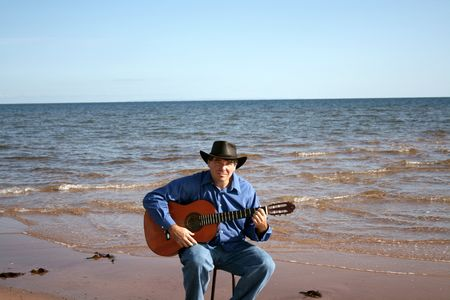 A man plays his guitar on the beach photo