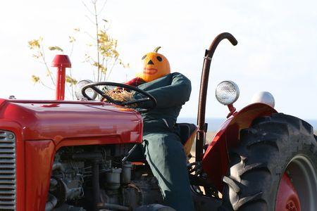 A pumpkin head drives a red tractor