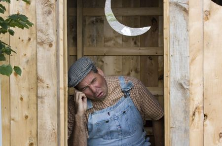 latrine: Man using outhouse