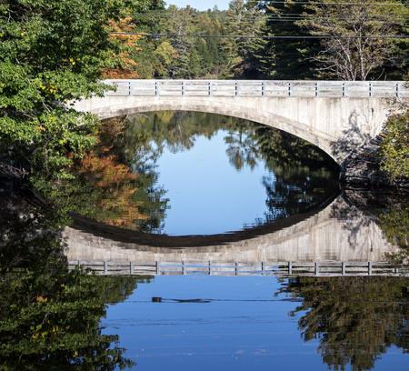 maine: reflection of a stone bridge maine Stock Photo