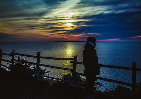 mujer mirando el horizonte: mujer viendo la salida del sol
