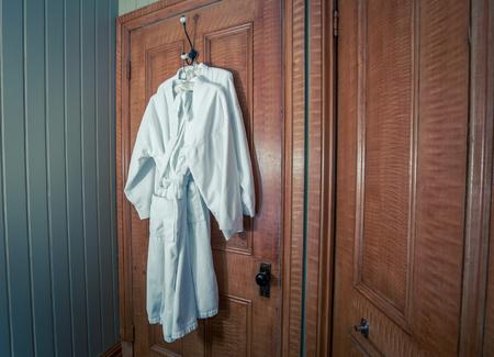 closet door: hanging white bathrobe