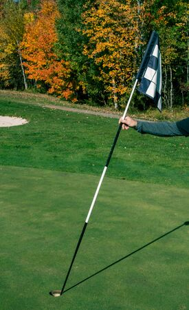 replacing a golf flag Stock Photo