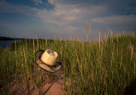 straw hat in beach grass Stock Photo