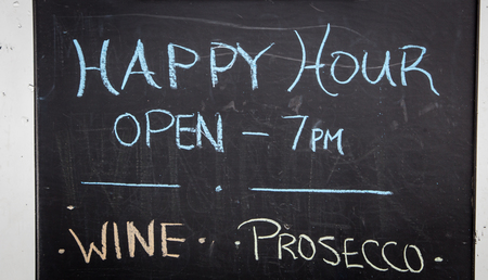 Happy hour sign on a chalkboard