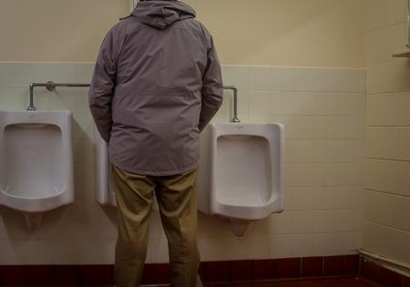 man using the urinal Archivio Fotografico