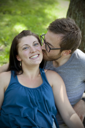 Young man kisses girlfriend on the cheek