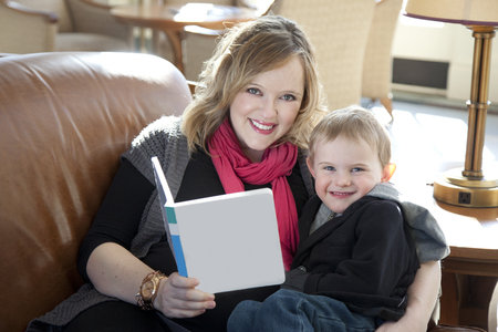 A mom reading a book to her son on a couch. 版權商用圖片