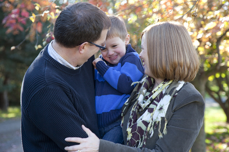 Mother, father and son having a hug and laughing together in the countryside in Autumn.