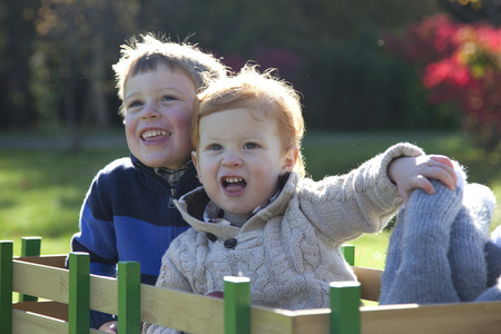 two boys ride and grin in a wagon Stock Photo
