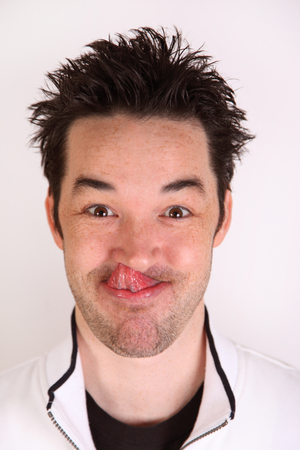 man sticks out tongue and picks nose