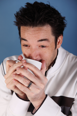savour: Young man warms up with hot mug.