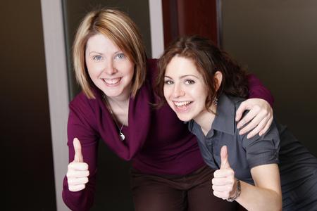 Twee aantrekkelijke onderneemsters glimlachen terwijl het werken aan project Stockfoto