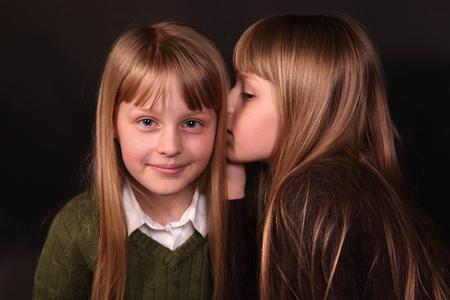 heard: twin girls share a secret Stock Photo