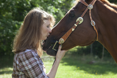 Side view of woman kissing muzzle of brown horse.
