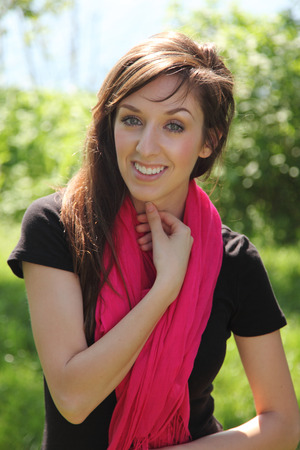 Beautiful young brunette with pink scarf smiles outdoors.