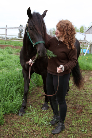 Red haired young woman in green field with horse.