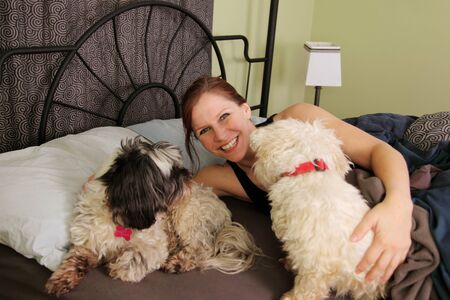 woman in bed with pets