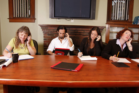employees at work on cellphones Stock Photo