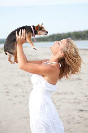 Pretty blond woman on a beach in a white dress, kissing a small Chihuahua dog.