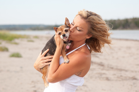 Pretty blond woman on a beach in a white dress, kissing a small Chihuahua dog Stock Photo