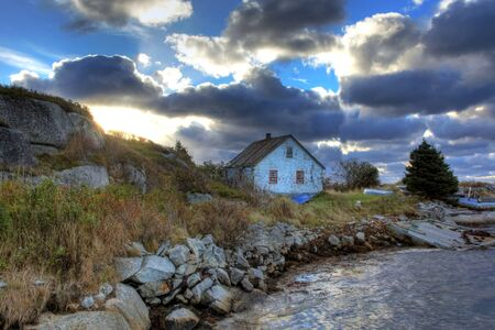 Small house at sunset on the shoreline Editorial
