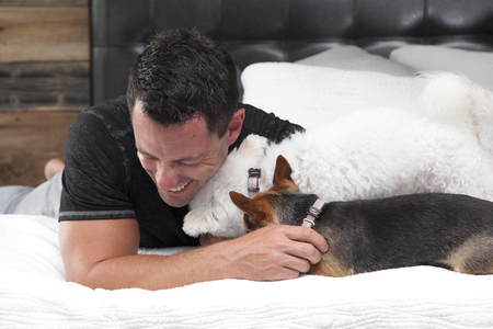 family tickle: two dogs kiss and lick their owner