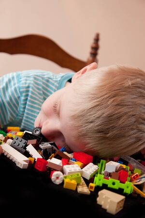 Tired little boy in bed falls asleep while playing with colorful Lego pieces, home background.
