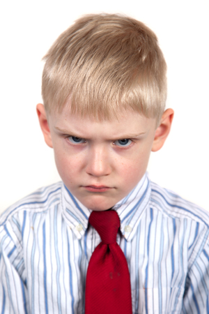 hostile: Little boy frowning angrily. Cranky face. Stock Photo
