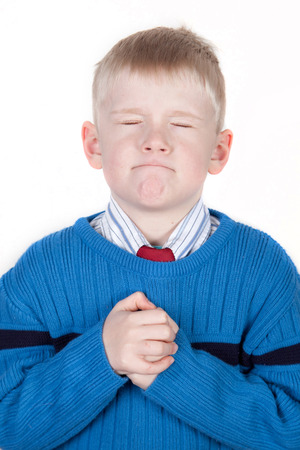 little boy clasps his hands, pleading, praying or wishing Stock Photo