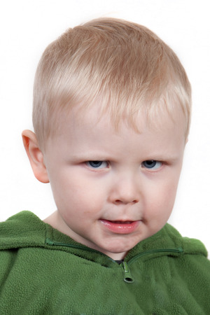 cranky: Toddler frowns angrily. Cranky face. Stock Photo